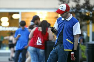 "Michael Young, dressed as Pokemon character Ash Ketchum, plays ""Pokemon Go, "" in Springfield, Mo. on Friday, July 15, 2016. ""Pokemon Go,"" a free mobile app partly owned by Nintendo, allows people to collect and battle Pokemon in the real world. (Guillermo Hernandez Martinez/The Springfield News-Leader via AP)"